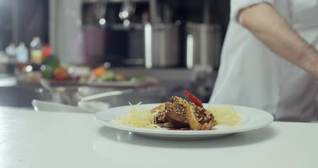 kazık : Asian chef serves a dish of meat on a plate adding the final decoration, before serving to the customer