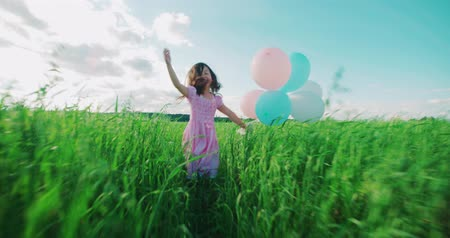 Çapraz kollar : little Asian girl in a dress running through green wheat field with balloons in hand, slow motion