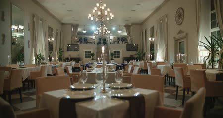 lux : an empty restaurant hall, a table for two served candle light, ready to receive guests, dolly shot