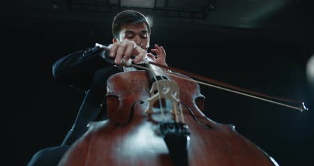 outstanding : asian cellist male solo classical music performance, black background