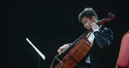 old pit : asian cellist male solo classical music performance, close-up