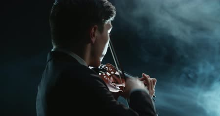 podfuk : Asian violinist soloist male performing at a concert of classical music, close-up