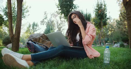 segregatory : girl student with a laptop in the park typing on the keyboard doing the job