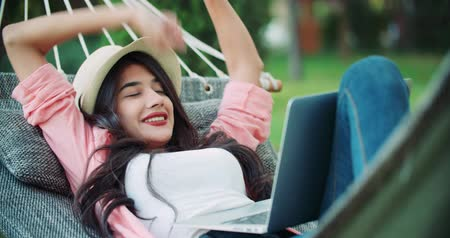 pursue : young successful girl blogger lies in a hammock with a laptop in the park, enjoys life at remote work