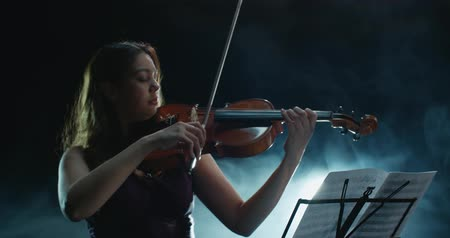 достигать : Violinist girl performing on stage, light, dark background