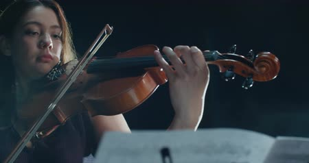 виолончель : detail shot, performance of violinist girl on stage, light, dark background