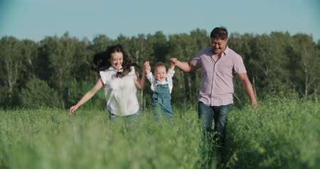 az egészséges életmód : happy Asian family with small child 1 year running on the green field, slow motion