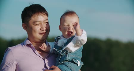 paternal : happy Asian father holds his son for 1 year, the baby laughs happily, slow motion Stock Footage