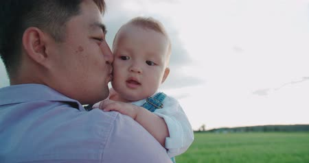 paternal : portrait of happy Asian father holds his son for 1 year, slow motion, Sunny day