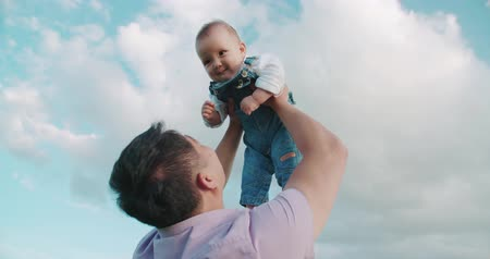 paternal : portrait of happy Asian father holds his son for 1 year, playing with the baby throws up, slow motion Stock Footage