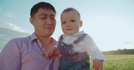 oddanost : portrait of happy Asian father holds his son for 1 year, slow motion, Sunny day