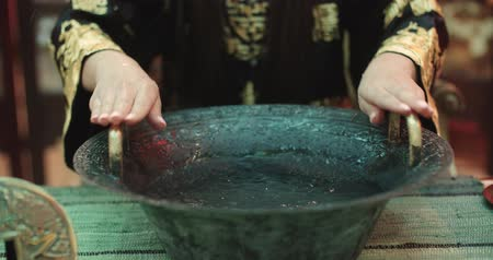 gong : beautiful Chinese girl uses a magic singing bowl with  boiling water effect, close up