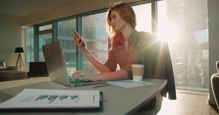 napirend : Young business woman sitting at a desk in a modern office in a skyscraper work, preparing for presentations, sun glare, steadicam shot Stock mozgókép