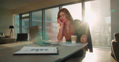 napirend : Young business woman sitting at a desk in a modern office in a skyscraper works, create a presentation, glare of the sun, steadicam shot