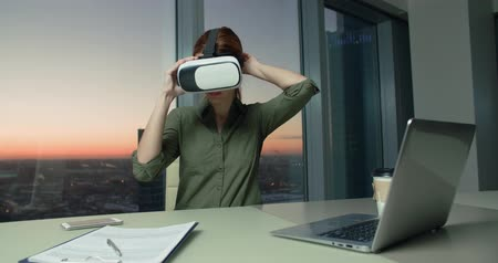 exited : Technology VR-businessman young girl wears and uses virtual reality technology VR Glasses to work in modern office in a skyscraper. the creation of the presentation