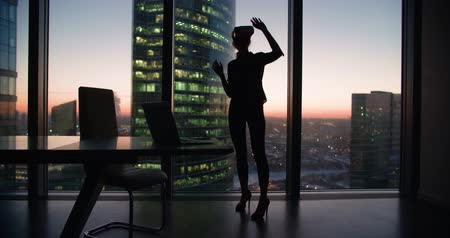 exited : silhouette Technology VR-businessman young girl wearing virtual reality technology VR Glasses to work in modern office in a skyscraper. the creation of the presentation