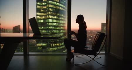 честолюбивый : young woman businessman ceo after a day with a cup of coffee in the hands of the panoramic windows in a skyscraper office, dolly shot
