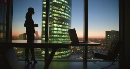 ambition : young woman businessman drinking coffee standing at the panoramic windows in a skyscraper office at sunset
