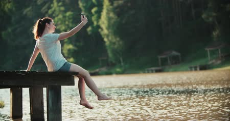 dangle : A woman relaxes on the shore of the lake, sitting on the edge of the wooden pier , swing legs at the water surface,photographing themselves on the smartphone selfie.