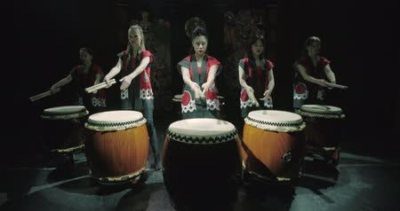 musical intrument : a group of Japanese Taiko drummers girls , start playing  dark background, slow motion