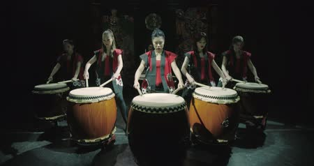 taiko drums : a group of Japanese Taiko drummers girls , start playing with the jump dark background, slow motion