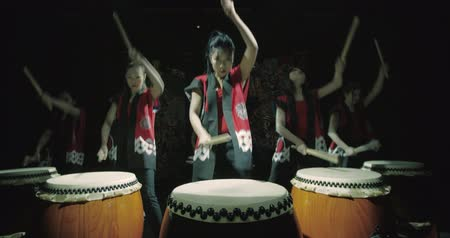 musical intrument : a group of Japanese Taiko drummers girls , start playing with the jump dark background, slow motion