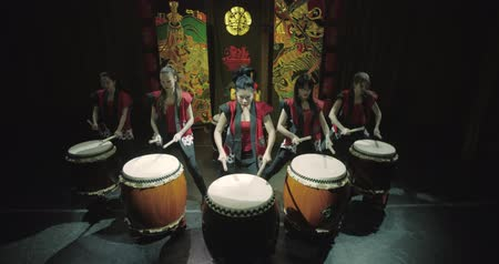 musical intrument : a group of Japanese Taiko drummers girls performs on stage,a dark background