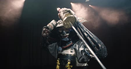 frightful : Japanese samurai in the historical suit threatens with a sword , posing for the camera, slow motion Stock Footage
