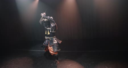 ameaça : Japanese samurai in the historical suit threatens with a sword , posing for the camera, slow motion Stock Footage