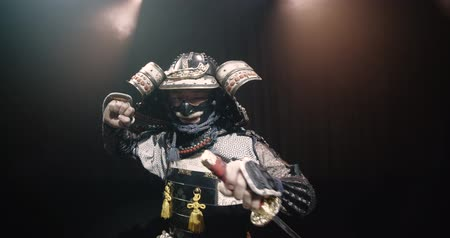 sinir : Japanese samurai in the historical suit threatens with a sword , posing for the camera, slow motion Stok Video