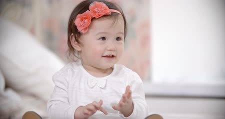 girl claps : portrait of little Asian baby girl having fun playing in the room, smiling and laughing, slow motion.