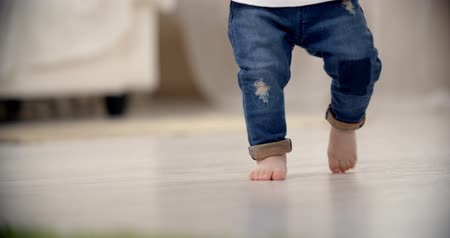 know : little girl Asian baby taking its first steps, close up, slow motion Stock Footage