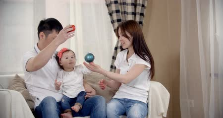 утешитель : family idyll,a young Asian family  fun play at home on the sofa with the baby 1 year, slow motion