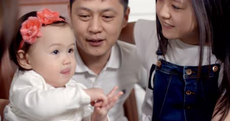 пуховое одеяло : family idyll,a young Asian family with two daughters, a fun play at home on the bed with the baby 1 year, slow motion