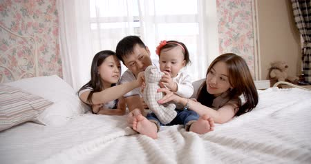 утешитель : family idyll,a young Asian family with two daughters, a fun play at home on the bed with the baby 1 year, slow motion