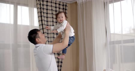paternal : young Asian father playing with her baby holding, happy emotions, baby laughing slow motion Stock Footage
