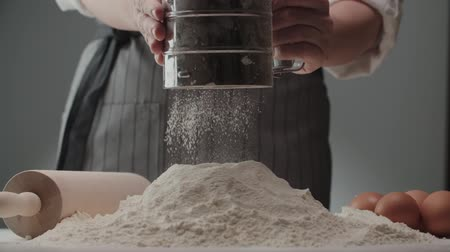 sieving : the chef sifts flour for kneading dough , close-up, slow motion Stock Footage