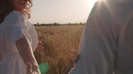 вести : Follow me, young happy couple running through a field of Golden wheat at sunset, slow motion, flare, flowing hair