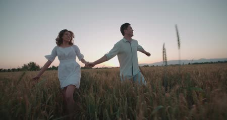 casal heterossexual : Happy couple having fun outdoors. Couple running away on the wheat field, sunset, slow motion