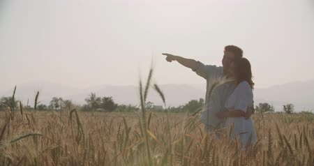 raised : Beauty Couple relaxing on wheat field together, slow motion