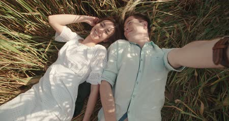 self portrait photography : young lovely couple lying in a field of wheat, having a good time and taking selfies Stock Footage
