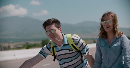 another : young couple standing on an empty road, hitchhiking, mountainous terrain, slow motion