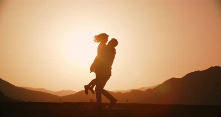 dospělí : Romantic young couple silhouette. Woman running to her man and they hug and spin at sunset Golden hour, slow motion