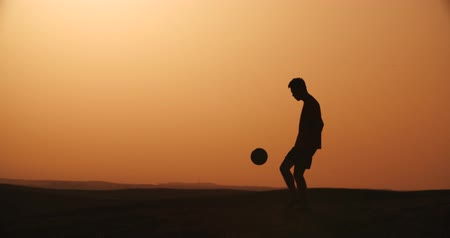 sertés : football player silhouette , practicing with the ball,the sunset Golden hour, slow motion