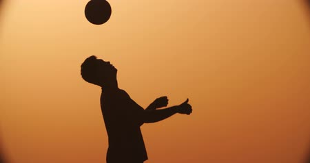 sertés : football player silhouette , practicing with the ball,the sunset Golden hour,heading slow motion