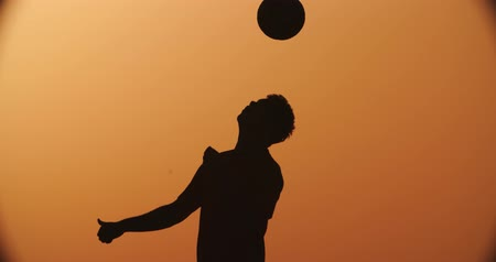human foot : football player silhouette , practicing with the ball,the sunset Golden hour,heading slow motion