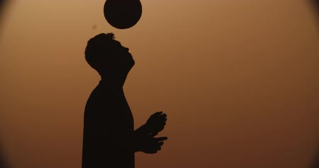 brezilya : football player silhouette , practicing with the ball,the sunset Golden hour,heading slow motion