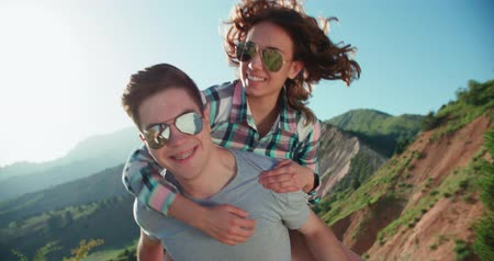 glare : Happy Couple Having Fun Outdoors in the background mountains sunset time,slow motion . Laughing Joyful Family. Freedom Concept Stock Footage