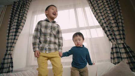 image house : two little boy of Asian appearance, having fun on the sofa in the room, jump and laugh