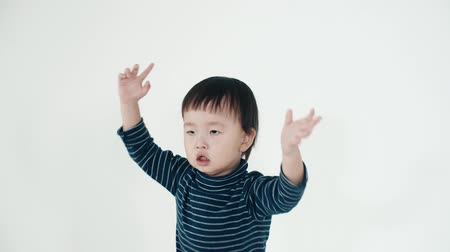 brothers : Asian boy 5 years old funny dance on white background,close up